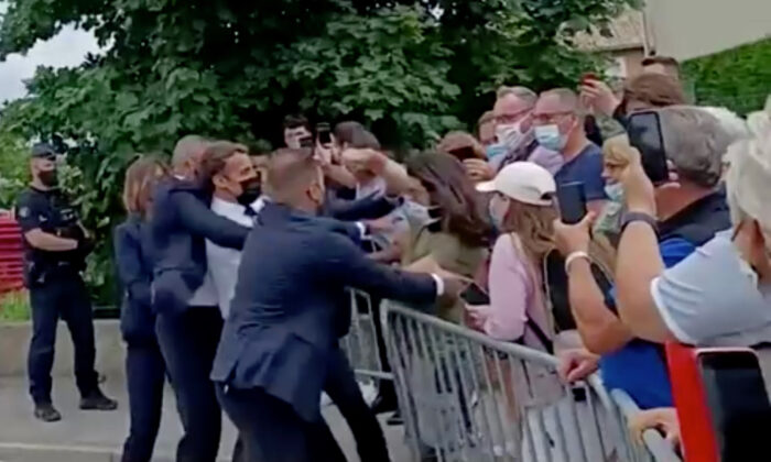 French President Emmanuel Macron is slapped in the face by a member of the public during a visit to Tain-l'Hermitage, France, on June 8, 2021. (BFMTV via Reuters TV)