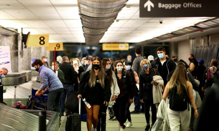 Travelers wearing face masks reclaim their luggage at the airport in Denver, Colorado, on Nov. 24, 2020.  (Kevin Mohatt/Reuters)