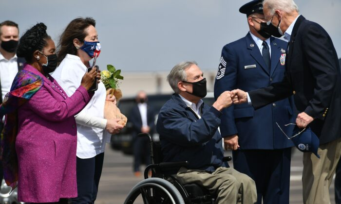 President Joe Biden (R) greets Texas Governor Greg Abbott and his wife Cecilia Abbott (2nd L) at Ellington Field Joint Reserve Base in Houston, Texas, on Feb. 26, 2021. Also welcoming the president is Rep. Sheila Jackson Lee (L). (Mandel Ngan/AFP via Getty Images)
