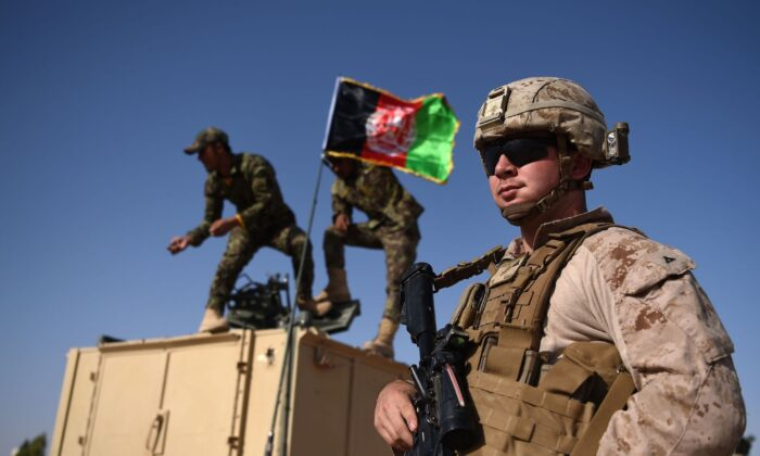 A U.S. Marine looks on as Afghan National Army soldiers raise the Afghan National flag on an armed vehicle during a training exercise at the Shorab Military Camp in Helmand Province, Afghanistan on Aug. 28, 2017. (Wakil/Koshar/AFP via Getty Images)