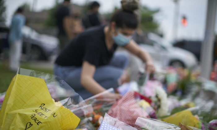 A woman arranges flowers at the scene of Sunday's hate-motivated vehicle attack in London, Ont. on June 8, 2021, in honour of the four members of a Muslim family that died and the youngest boy who is in hospital. (The Canadian Press/ Geoff Robins)