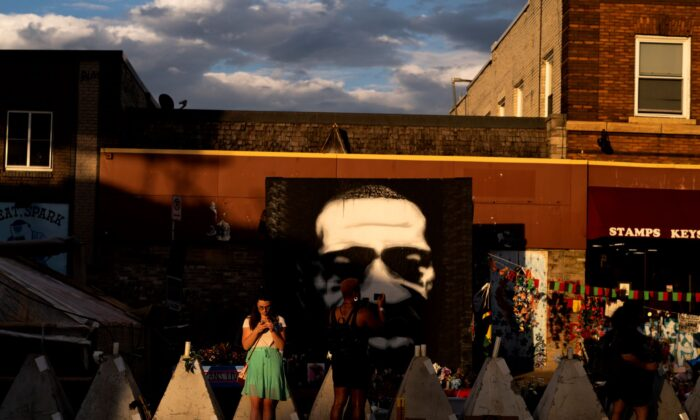 People look on a portrait of George Floyd at George Floyd Square in Minneapolis, Minn., on June 3, 2021. (Stephen Maturen/Getty Images)