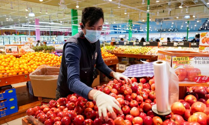 Wearing a mask and gloves, a worker re-stocks apples in an Asian grocery store in Falls Church, Va., on April 3, 2020. (Kevin Lamarque/Reuters)