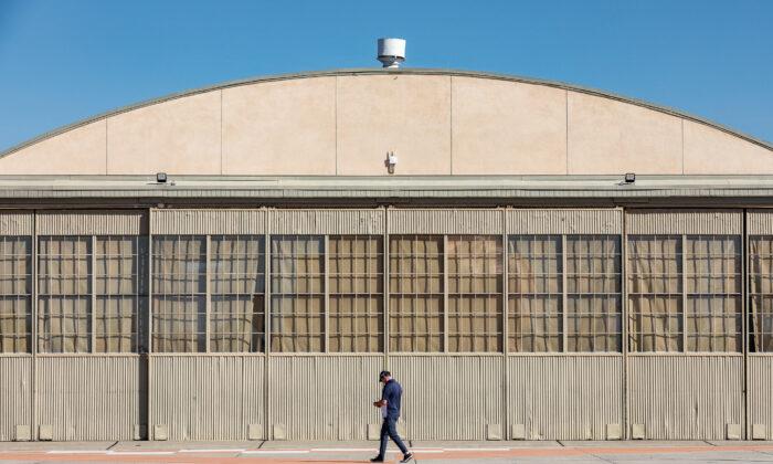 A man walks past Hangar 244 at The Orange County Great Park in Irvine, Calif., on Jan. 26, 2021. (John Fredricks/The Epoch Times)