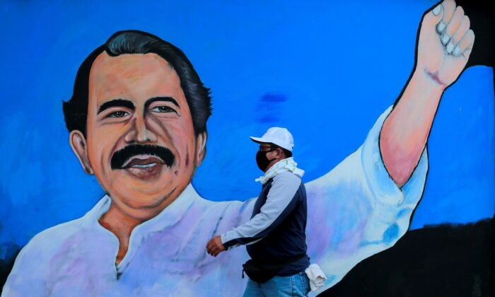 A man wearing a face mask walks by a mural depicting Nicaraguan President Daniel Ortega, in Managua, Nicaragua on March 30, 2020. (Oswaldo Rivas/Reuters)