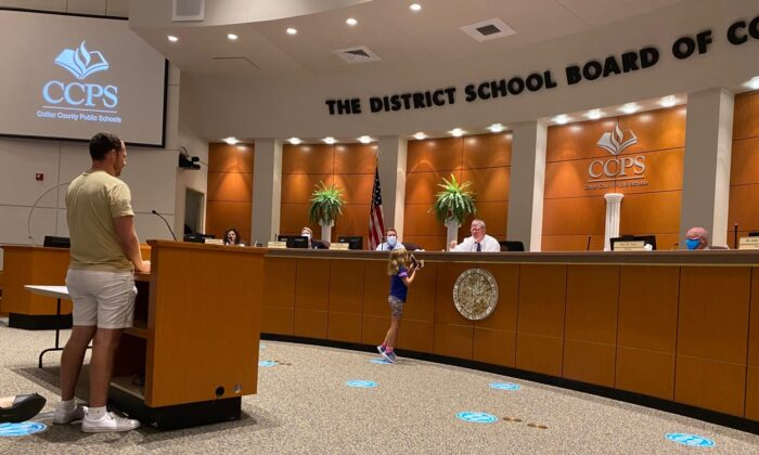 Dan Cook addresses the Collier County School Board regarding his concerns of CRT content in textbooks as his daughter Selah distributes Pocket Constitution booklets to each member in the district's classrooms, on May 7, 2021. (Patricia Tolson/The Epoch Times)