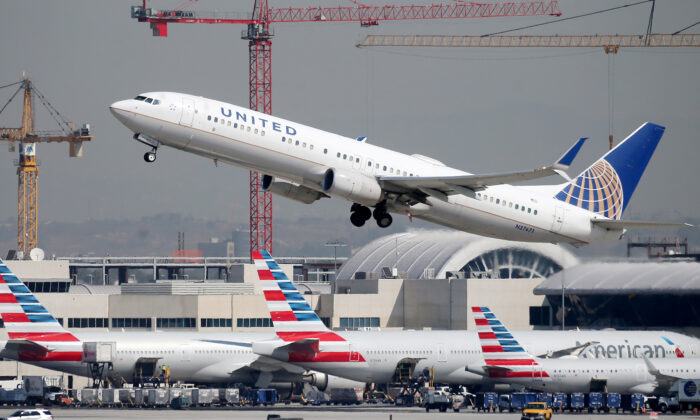 A United Airlines plane takes off above American Airlines planes on the tarmac at Los Angeles International Airport (LAX) on Oct. 1, 2020. (Mario Tama/Getty Images)