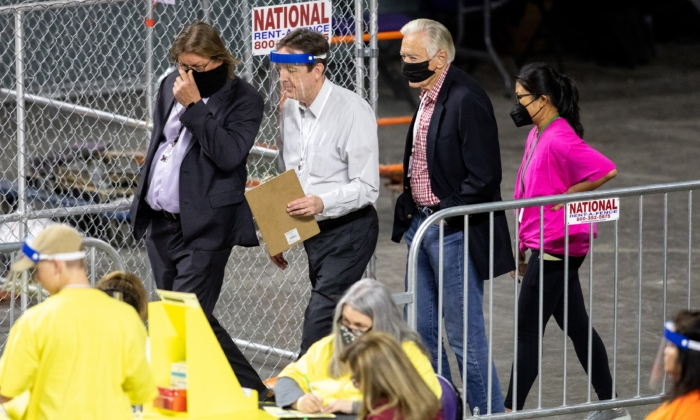 Former Arizona Secretary of State Ken Bennett (second from left) moves ballots during an election audit at Veterans Memorial Coliseum in Phoenix, Ariz., on May 1, 2021. (Courtney Pedroza/Getty Images)