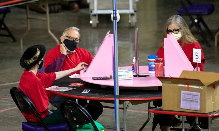 Contractors working for Cyber Ninjas, which was hired by the Arizona State Senate, examine and recount ballots from the 2020 general election at Veterans Memorial Coliseum in Phoenix, Ariz., on May 1, 2021. (Courtney Pedroza/Getty Images)