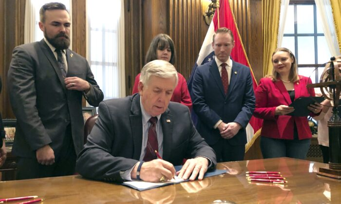 Missouri Gov. Mike Parson signs a bill banning most abortions in Jefferson City, Mo., on May 24, 2019. (Summer Balentine/AP Photo)