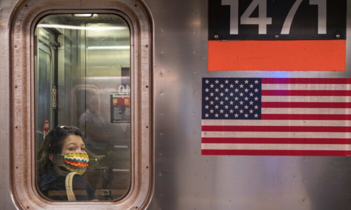 A person wearing a mask rides the subway during rush hour on the first day of phase one of the reopening after the CCP virus lockdown in New York City on June 8, 2020. (David Dee Delgado/Getty Images)