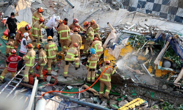 Firefighters search for survivors from a collapsed building in Gwangju, South Korea, on June 9, 2021. (Chung Hoi-sung/Yonhap via AP)