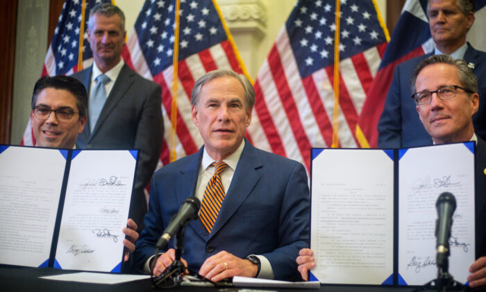(L-R) Texas state Rep. Chris Paddie, Texas Gov. Greg Abbott, and Texas state Sen. Kelly Hancock show off Senate bills 2 and 3 during a press conference at the State Capitol in Austin, Texas, on June 8, 2021. (Montinique Monroe/Getty Images)