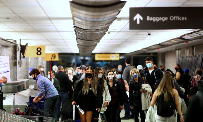 Travelers reclaim their luggage at the airport in Denver, Colorado, on Nov. 24, 2020. (Kevin Mohatt/Reuters)