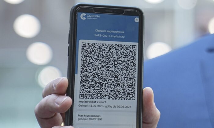 Jens Spahn (CDU), Federal Minister of Health, shows the app for the digital vaccination certificate at the regular press conference on the Corona situation in Berlin, Germany, on June 10, 2021.  (Michael Kappeler/DAP via AP)