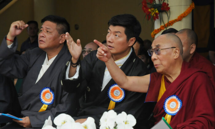 Tibetan spiritual leader the Dalai Lama (R), exile Tibetan Prime Minister Lobsang Sangay (C), and Speaker of the Tibetan Parliament-in-exile Penpa Tsering (L) gesture to a banner showing pictures of the Dalai Lama at different ages during his 77th birthday celebrations at the Tsuglakhang Temple in McLeod Ganj, Dharamsala, on July 6, 2012. The Tibetan leader, who fled his homeland for northern India in 1959 after a failed uprising against Chinese communist rule, announced in 2011 that he was giving up his political role to focus on spiritual duties. (STRDEL/AFP/GettyImages)