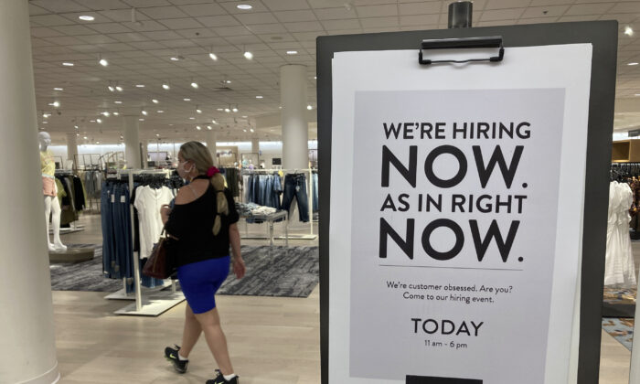 A customer walks behind a sign at a Nordstrom store seeking employees, in Coral Gables, Fla., on May 21, 2021. (Marta Lavandier/AP Photo)