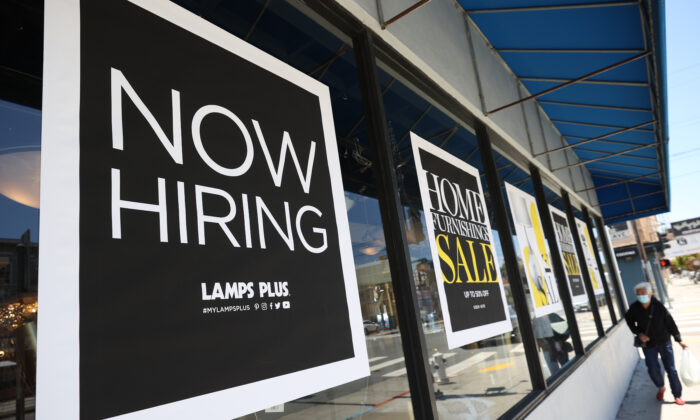 A pedestrian walks by a Now Hiring sign outside of a Lamps Plus store in San Francisco, Calif., on June 3, 2021. (Justin Sullivan/Getty Images)
