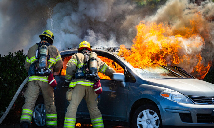 Orange County Fire Authority firefighters extinguish flames from a car that ignited. A suspect said to be under the influence of drugs was taken into custody by Irvine Police Department officers in Irvine Calif., on June 11, 2021. (John Fredricks/The Epoch Times)