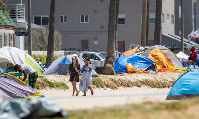 Women walk past homeless encampments in Venice Beach, Calif., on June 8, 2021. (John Fredricks/The Epoch Times)