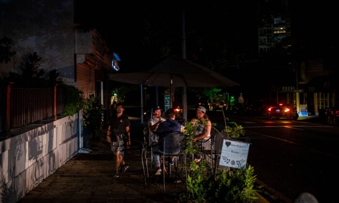 People are seen outside a restaurant on a dark usually busy street in San Juan, Puerto Rico, on June 10, 2021. (Ricardo Arguengo/AFP via Getty Images)