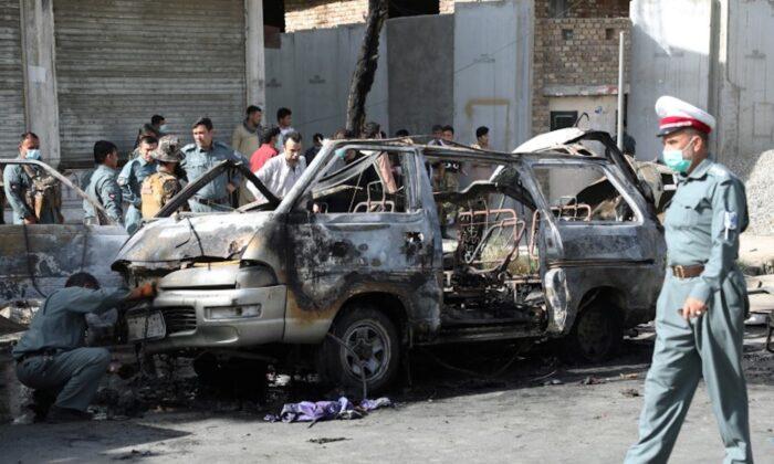 Afghan security forces inspect the wreckage of a passenger van after a blast in Kabul, Afghanistan on June 12, 2021. (Stringer via Reuters)