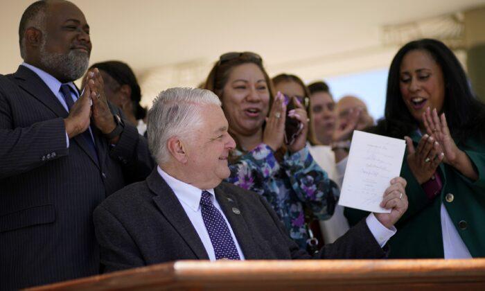 Nevada Gov. Steve Sisolak holds up a bill newly signed into law in Las Vegas, Nev., on June 11, 2021. (John Locher/AP Photo)