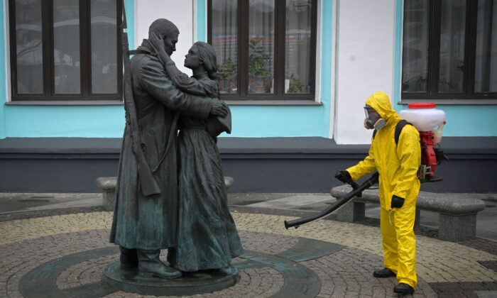 A serviceman of the Russian Ministry for Civil Defence, Emergencies, and Elimination of Consequences of Natural Disasters, wearing protective gear, disinfects Moscow's Belorussky railway station next to a statue, amid the COVID-19 pandemic, Russia, on June 11, 2021. (Natalia Kolesnikova/AFP via Getty Images)