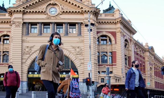 Pedestrians cross the road at Flinders Street Station in Melbourne, Australia, June 11, 2021. (Sandra Sanders/Reuters)