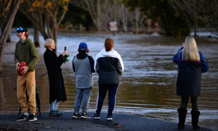 People are seen observing flood water in Traralgon, Victoria, Thursday, June 10, 2021. Thousands of Victorians have been left without power as wild winds and flooding hit the state. (AAP Image/James Ross)