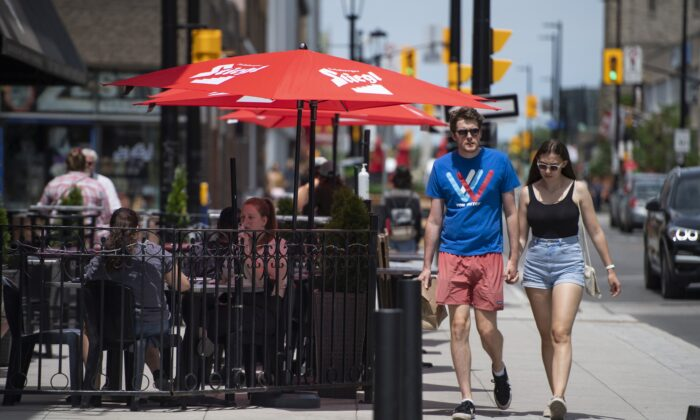 People walk past a restaurant patio open for business on the first day of Ontario's three-phase reopening plan, in Ottawa on June 11, 2021. (The Canadian Press/Justin Tang)