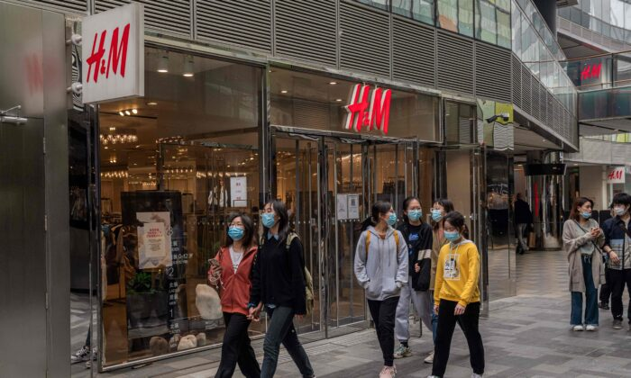 People walk past an H&M store in Beijing on April 5, 2021. (Nicolas Asfouri/AFP)