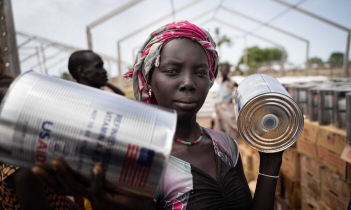 A woman from Murle ethnic group receives cans of oil during a food distribution by United Nations World Food Programme (WFP) in Gumuruk, South Sudan, on June 10, 2021, after her village was recently attacked by an armed youth group. (Simon Wohlfahrt/AFP via Getty Images)