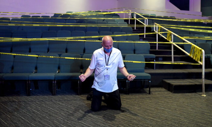 A man kneels to pray in front of seats cordoned off with caution tape due to the CCP virus at the International Church of Las Vegas in Las Vegas, Nev., on May 31, 2020. (Ethan Miller/Getty Images)