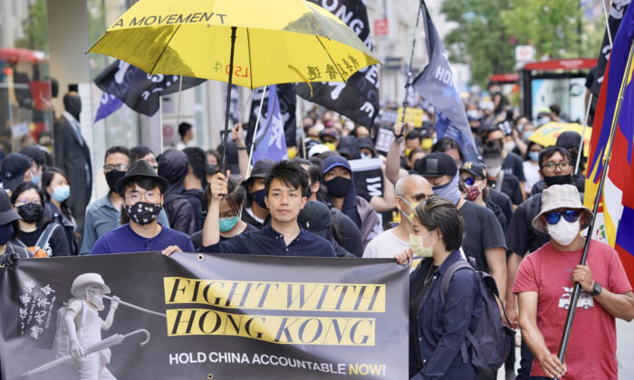 Simon Cheng (front left) and Finn Lau (center) in a march commemorating the two-year anniversary of Hong Kong's pro-democracy movement, in London on June 12, 2021. (Yanning Qi/The Epoch Times)