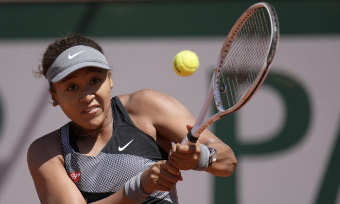 Japan's Naomi Osaka returns the ball to Romania's Patricia Maria Tig during their first round match of the French open tennis tournament at the Roland Garros stadium in Paris, France, on May 30, 2021. (Christophe Ena/AP Photo)