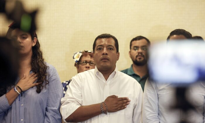 Nicaraguan opposition activist Felix Maradiaga (C) stands at attention as the national anthem is sung during a press conference in Managua, Nicaragua, on Sept. 18, 2019. (Alfredo Zuniga/AP Photo)