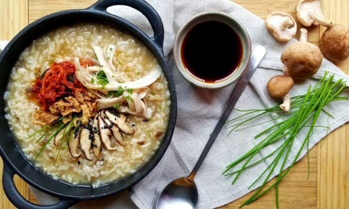 This juk starts with a flavorful homemade chicken stock, and is finished with vibrant toppings including kimchi, pan-fried mushrooms, black sesame seeds, and fresh chives. (Judy Joo)