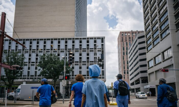 Medical workers and pedestrians cross an intersection outside of the Houston Methodist hospital in Houston, Texas on June 9, 2021. (Brandon Bell/Getty Images)