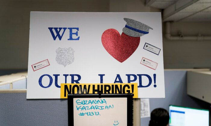 """A """"Now Hiring"""" sign is placed on a cubicle wall in the office of the Los Angeles Police recruitment and employment division in Los Angeles, Calif., On Sept. 9, 2020. (Jae C. Hong/AP Photo)"""