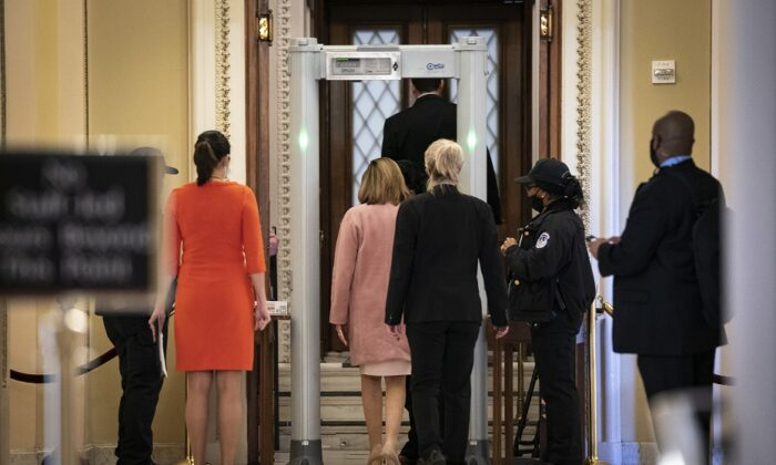Speaker of the House Nancy Pelosi (D-Calif.) walks through a metal detector before entering the House Chamber at the U.S. Capitol in Washington on Jan. 21, 2021. (Drew Angerer/Getty Images)