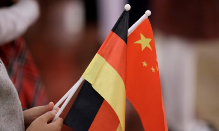 A student holds flags of China and Germany before a welcome ceremony hosted by Chinese leader Xi Jinping for German President Frank-Walter Steinmeier at the Great Hall of the People in Beijing, China, on Dec. 10, 2018. (Jason Lee/Reuters)