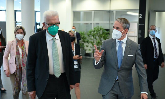The Governor of Baden-Wuerttemberg, Winfried Kretschmann, front left, and Martin Jetter, front right, CEO of IBM Europe, attend the official inauguration of the first commercially used quantum computer in Europe in Ehningen, Germany, on June 15, 2021. (Bernd Weissbrod/dpa via AP)