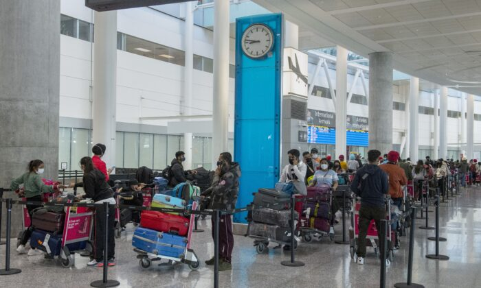 International travellers wait in long lines for transportation to their quarantine hotels at Pearson Airport in Toronto on April 23, 2021. (The Canadian Press/Frank Gunn)