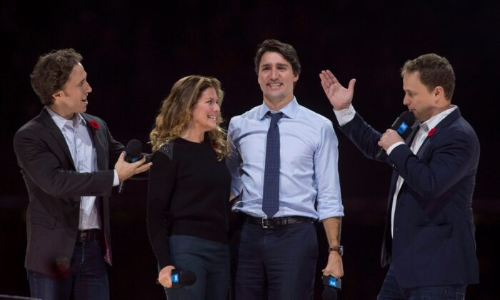WE Charity co-founders Craig (L) and Marc Kielburger introduce Prime Minister Justin Trudeau and his wife Sophie Gregoire Trudeau as they appear at WE Day celebrations in Ottawa on Nov. 10, 2015. (The Canadian Press/Adrian Wyld)