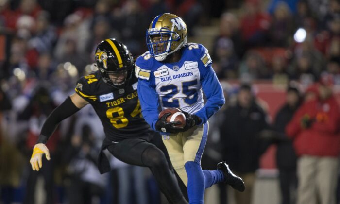 Hamilton Tiger-Cats' Nikola Kalinic chases Winnipeg Blue Bombers' Nick Taylor during the 107th Grey Cup in Calgary on Nov. 24, 2019. The 108th Grey Cup will be held in Hamilton on Dec. 12, 2021. (The Canadian Press/Jeff McIntosh)