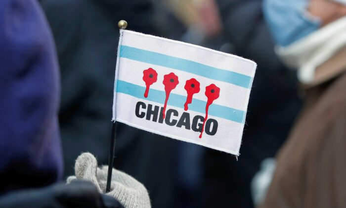 A woman holds a small flag depicting bullet holes with blood during an anti gun violence march on the Magnificent Mile in Chicago, Ill., on Dec. 31, 2020. (Kamil Krzaczynski/AFP via Getty Images)
