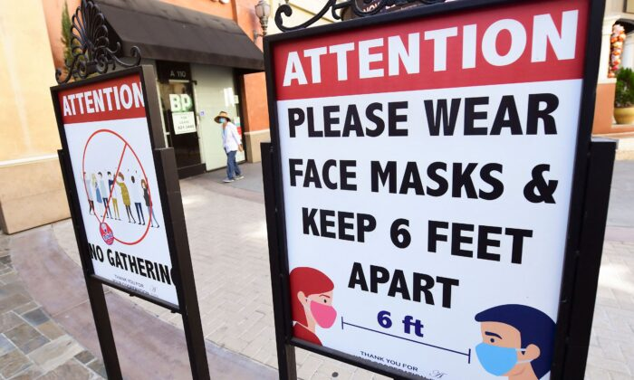 Signs reminding people of social distancing and wearing face masks remain at a mall in Monterey Park, Calif., on June 14, 2021. (Frederic J. Brown/AFP via Getty Images)