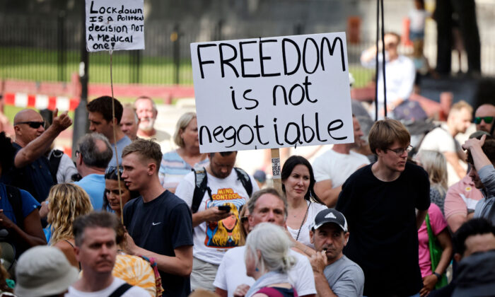 Protesters hold up placards at a demonstration against government lockdown restrictions in Parliament Square in central London on June 14, 2021. (Tolga Akmen/AFP via Getty Images)