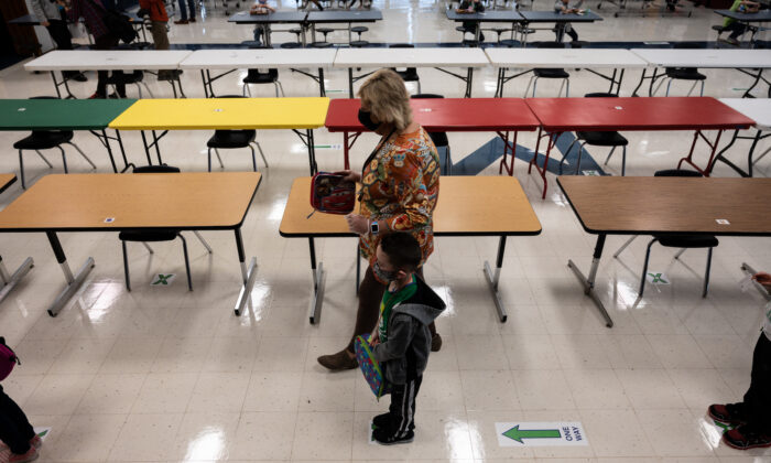 A masked teacher walks by as students wait in a single file line after eating a socially distanced lunch at Medora Elementary School in Louisville, Ky., on March 17, 2021. (Jon Cherry/Getty Images)